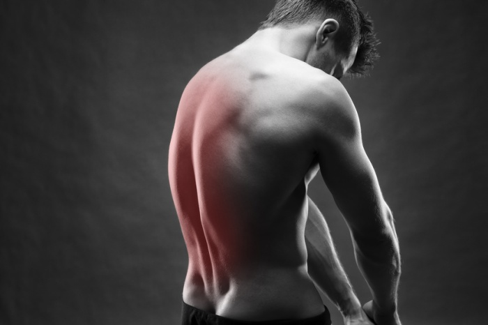 Man with backache. Pain in the human body. Muscular male body. Handsome bodybuilder posing on gray background